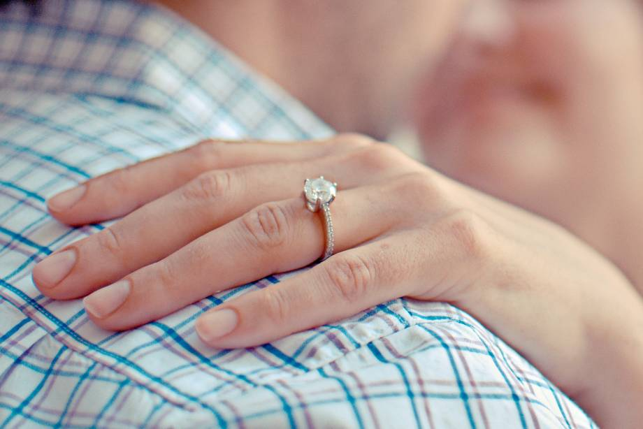 A Moissanite Ring is Sitting on a Woman's Hand as it Rests Upon a Man's Shoulder